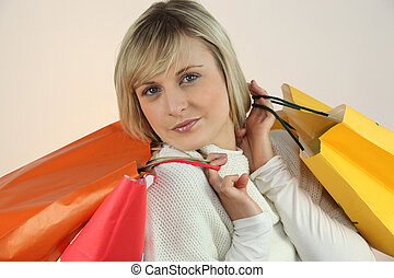 Young woman with arms full of storebags
