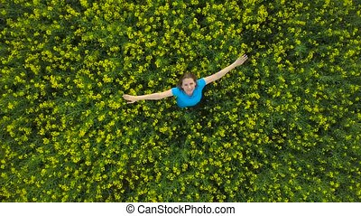 Young woman with arms outstretched in a yellow canola field