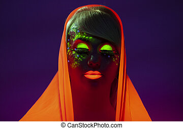 Young woman with artistic colorful makeup and orange scarf on her head, with closed eyes, isolated purple background.