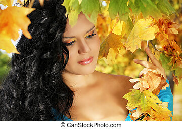 Young woman with autumn leaves fall yellow maple garden background