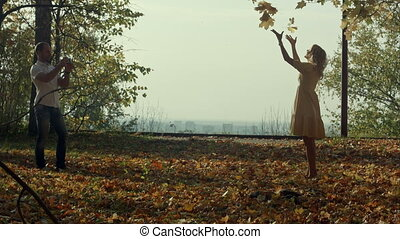 Young woman with autumn leaves in hand and fall yellow maple