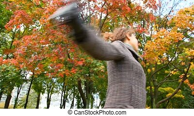 young woman with autumn red leaves in hand turning around in park