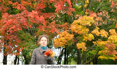 young woman with autumn red leaves in hand walking to camera in park
