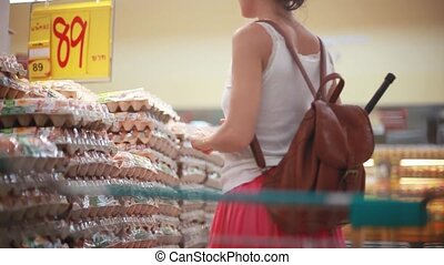 Young woman with backpack buys eggs at the supermarket puts...