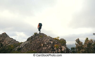 Young woman with backpack climbs a sharp ridge and reaches the top of a mountain. Lady on the top of a mountain among tropical plants in beautiful scenery on Canary Islands