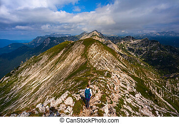 Young woman with backpack hiking along the path in the Vogel mountain, Slovenia