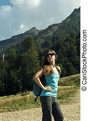 Young woman with backpack hiking in the mountains