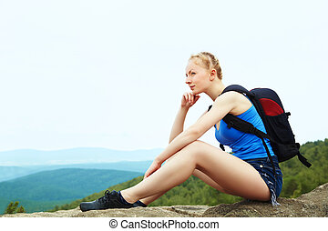 woman with backpack hiking in the mountains