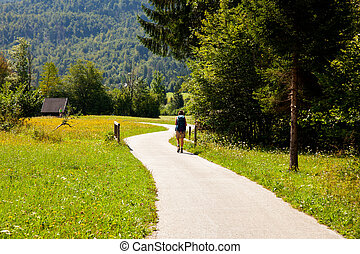 Young woman with backpack hiking in the Slovenian countryside