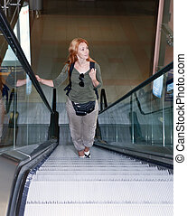 young woman with backpack on the escalator