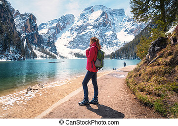 Young woman with backpack on the snowy shore of Braies lake