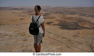 Young woman with backpack standing on cliff's edge and enjoying the desert view