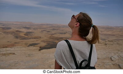 Young woman with backpack standing on cliff's edge looking at sky and turning around