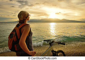 Young woman with backpack standing on the shore near his...