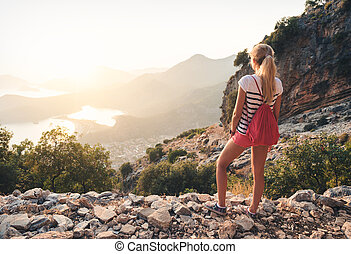 Young woman with backpack standing on the hill