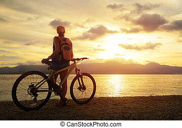 Young woman with backpack standing on the shore near his bike and enjoying the sunset over the sea on the background of the island