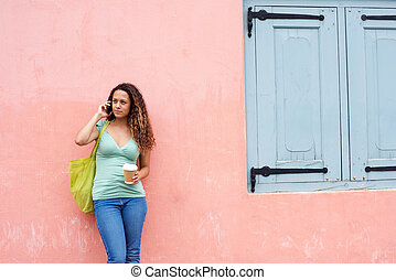 Young woman with bag talking on mobile phone
