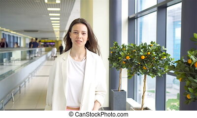 Young woman with baggage in international airport walking with her luggage. Airline passenger in an airport lounge waiting for flight aircraft.