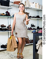 Young woman with bags in shoes store.