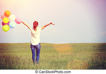 young woman with balloons - young asian woman running and...