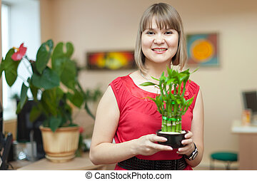 Young woman with bamboo plant