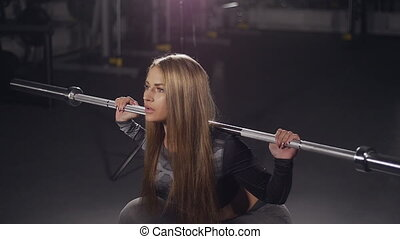 Young woman with beautiful athletic body doing exercises with barbell