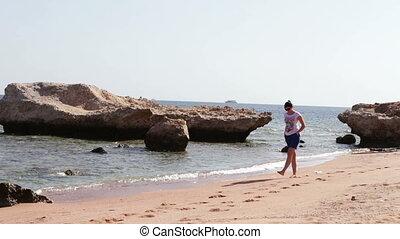 Young woman with beautiful legs walking away along clean golden sandy beach
