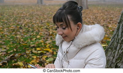 Young woman with beautiful make-up starts talking on the phone, smiling, sitting on fallen autumn leaves in park.