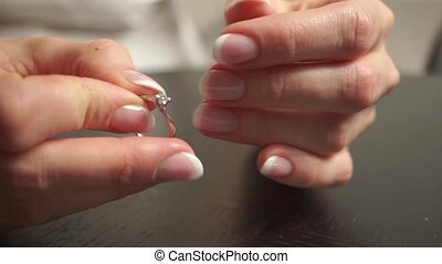 Young woman with beautiful nail polish putting a diamond ring on her finger