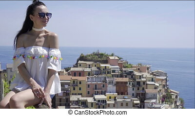 Young woman with beautiful view at old village in Cinque Terre, Liguria, Italy. European italian vacation.