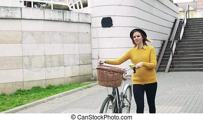 Young woman with bicycle in sunny spring town.