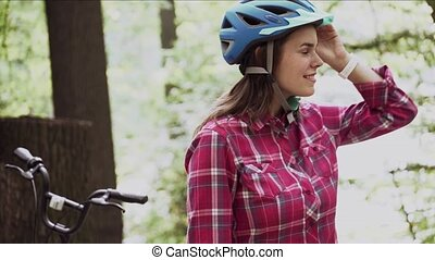 Young woman with bike stands in park. Portrait of young beautiful girl standing near bicycle, posing and smiling ,wearing a red checkered shirt in forest. Subject ecological mode of transport bicycle.