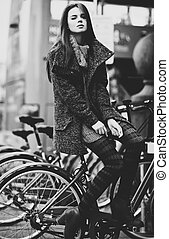 Young woman with bike - Young woman sitting at city bike. ...