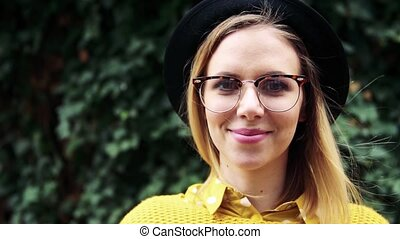 Young woman with black hat and glasses in sunny spring town....
