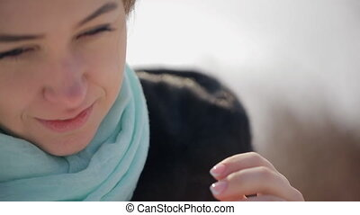 Young woman with blond hair and blue scarf looks directly,