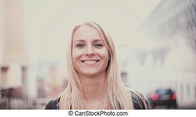 Young woman with blonde hair looking at camera and smiling. Portrait of beautiful girl in the city blur background.