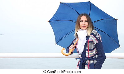 Young woman with blue umbrella