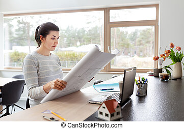 young woman with blueprint working at home office - remote ...