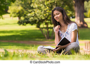 Young woman with book and pen sitting in park