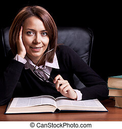 young woman with book at the desk on black background
