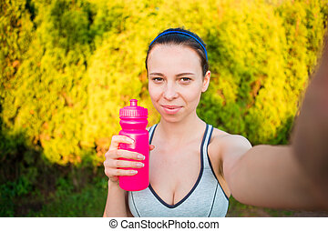 Young woman with bottle of water after running outside. Female fitness model training outside and taking selfie in the park. Healthy wellness fitness lifestyle.