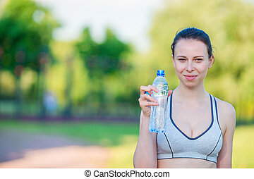 Young woman with bottle of water after running outside. Female fitness model training outside in the park. Healthy wellness fitness lifestyle.