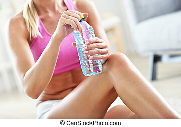Young woman with bottle of water after workout