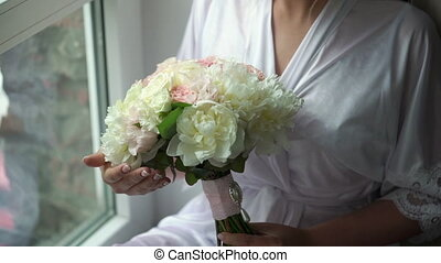 Young woman with bouquet in bathrobe
