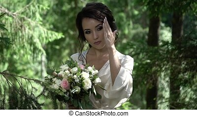 Young woman with bouquet in forest