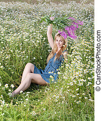 young woman with bouquet of firetop flower in the field