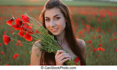 Young woman in red dress holding bouquet of red poppies, standing among poppies field, enjoying free time, resting on nature, smiling, flirting, winking, touching her hair.