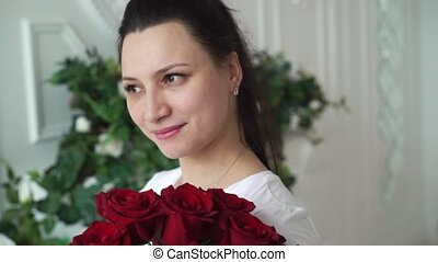 Young woman with bouquet of red roses
