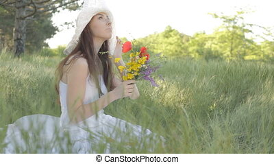Young woman with bouquet of wild fl
