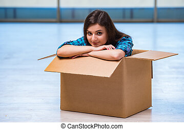 Young woman with box in moving house concept
